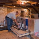 Vince Youndt, president of Vertex Mechanical, checks on the upper end of a split system installed in an attic.