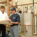 Joe Starr, left, reviews the water heater installation plan at a school near Pittsburgh.